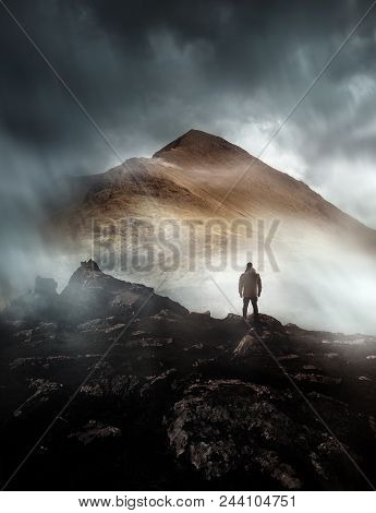 A Person Hiking Looks Onwards At A Mountain Shrouded In Mist And Clouds With The Peak Visible. Sceni