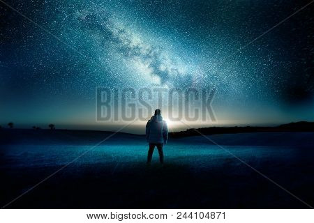 A Man Stands Watching With Wonder And Amazement As The Moon And Milky Way Galaxy Fill The Night Sky.