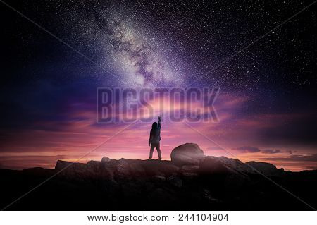 Night Time Long Exposure Landscape Photography. A Man Standing In A High Place Reaching Up In Wonder