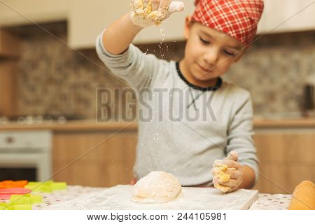 Cheerful Boy Making Dough For Biscuits. A Boy Pouring Dough With Flour. Child Making Cookies Using B