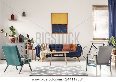 Real Photo Of A Navy Blue Sofa With Orange Cushions And An Artwork Above In Bright And Spacious Livi