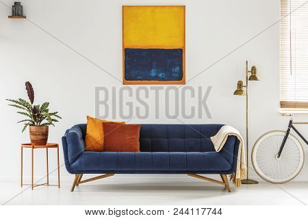 White Living Room Interior With Royal Blue Lounge, Modern Art Painting, Gold Lamp, Fresh Plant On Me