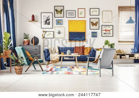 Simple Posters Gallery Hanging On The Wall In Bright Living Room Interior With Blue Sofa, Two Armcha