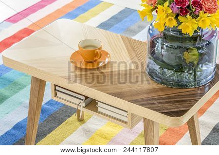 Close-up Of A Wooden Table With A Cup Of Coffee And A Bouquet Of Spring Flowers Standing On A Colorf