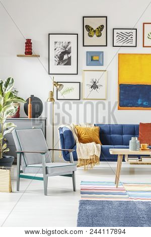 Real Photo Of A Boho Living Room Interior With A Gallery Of Posters Hanging On White Wall Above A Gr