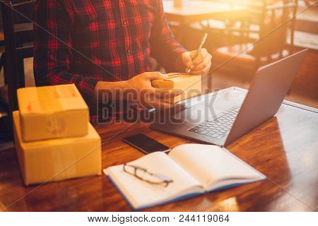 The Man Working Laptop Computer From Home On Wooden Floor With Postal Parcel, Selling Online Ideas C