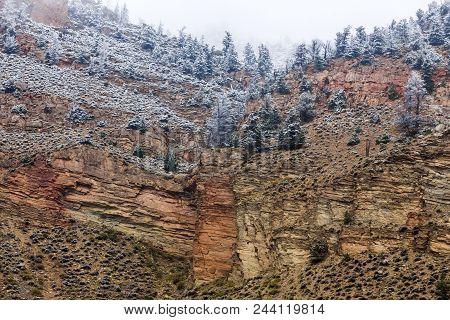Wyoming Mountain With Rock Layers And Fault Lines; Light Snow