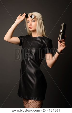 Attractive Stylish Woman In Black Leather Dress With Small Silver Bag And Watch. Fashion Concept.