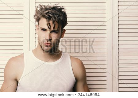 Man With Fair Hair On Light Wooden Planks Background. Macho With Seductive Face And Confident Look.