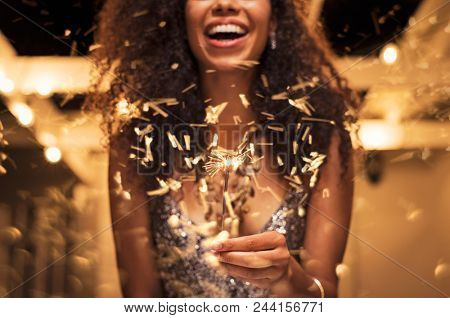 Cheerful young woman holding single sparkler in hand outdoor. Detail of african girl celebrating new year's eve with bengal light. Closeup of beautiful woman holding a sparkling stick at party night.
