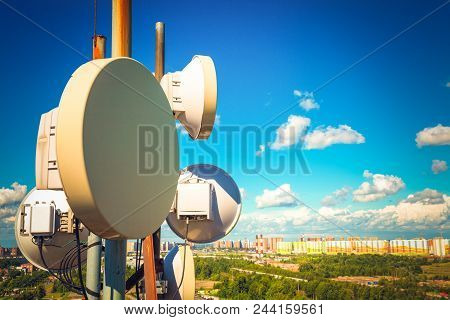 Telecommunication equipment with TV antennas, satellite dish and microwave antennas of mobile operators against blue sky with clouds and city. poster