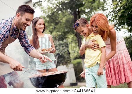 Young Family Make Barbecue At Their Home
