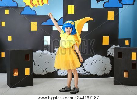 Cute girl in superhero costume against comic strip themed decoration