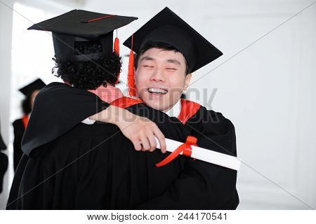 Happy students in bachelor robes hugging indoors, Graduation day