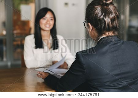 Business, career and placement concept -photo from back of businesswoman interviewing and talking with female applicant during job interview