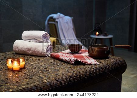 Spa And Wellness Setting With Rolled Spa Towels, Candles And Aroma Oil  In A Sauna Room