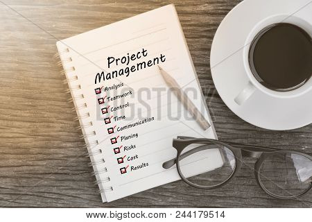 Project Management And Check List Marks In Notebook With Glasses, Pencil And Coffee Cup On Wooden Ta