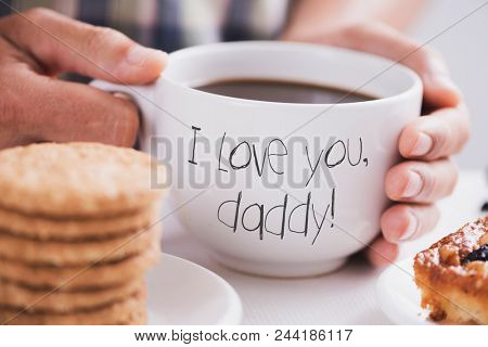 closeup of a caucasian man with a white ceramic cup with coffee in his hands, with the text I love you daddy written in it, at a table set for breakfast