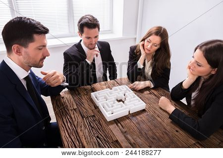 Group Of Young Businesspeople Trying To Solve Maze Puzzle At Workplace