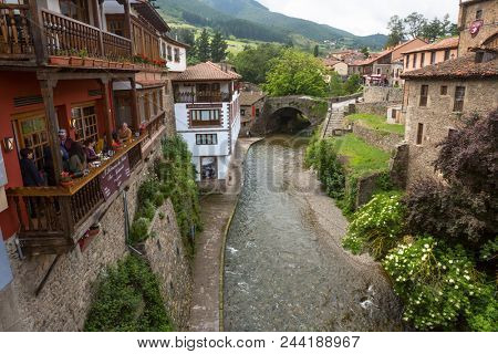 Potes, Spain - June 1, 2018: The river and traditional houses in the ancient Spanish town. Northern Spain, Cantabria.