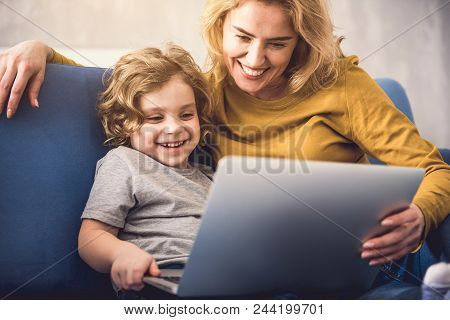 Smiling Mom And Kid Are Watching On Laptop Screen. They Are Sitting On Divan And Enjoying Time Toget