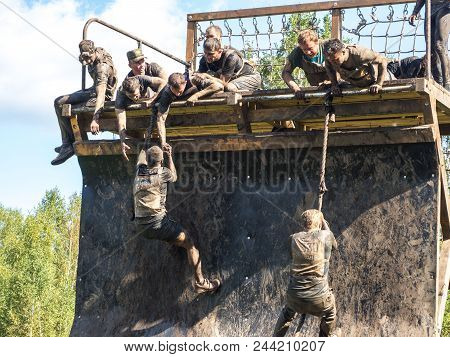 Novosibirsk, Russia - 2 September 2017: Young People Pass The Obstacle Course. Mud Race Runners. Ris