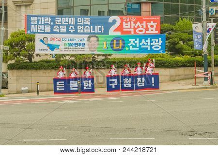 Daejeon, South Korea; June 7, 2018: Campaign Volunteers Standing On Corner Holding Signs And Waving