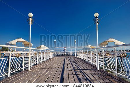 Tourist Woman In Red Hat And Striped Dress Standing On The Pier In Ruh Ordo Cultural Complex Issyk K