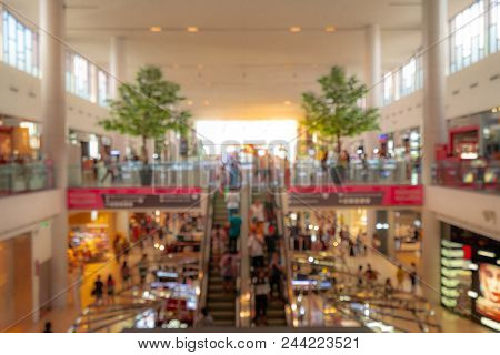 Blurred Shopping Mall Background. People Walking And Shopping On Holiday. People In Escalators At Th