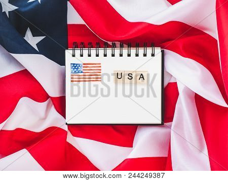 Notepad With Blank Page, Wooden Letters Of The Alphabet In The Form Of The Word Us On The Background