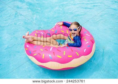 Child In Swimming Pool On Donut Float