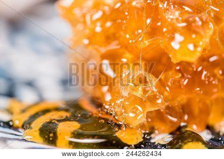 Honey Stands Drip Into Pool Below Comb