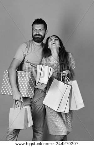 Family Shopping. Couple In Love Holds Shopping Bags On Yellow Background. Shopping And Spending Conc