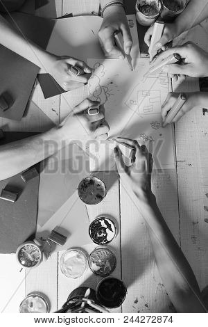 Artists Wooden Table With Paints And Colored Paper. Art And Artwork Concept. Hands Hold Colorful Mar