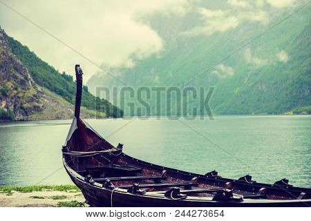 Old Wooden Viking Boat On Seashore In Norwegian Nature, Foggy Misty Day. Mountains And Fjord Sognefj