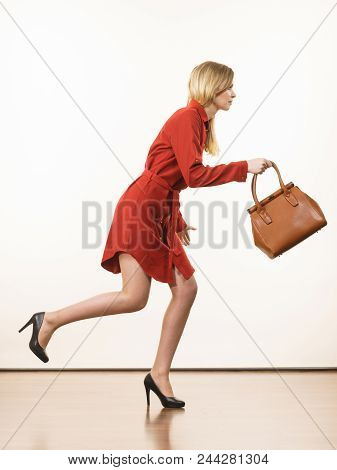 Fashionable Pretty Young Woman Wearing Elegant Casual Red Short Dress And Holding Leather Bag Runnin
