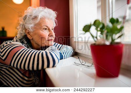 Sad Alone Senior Woman Looking Through Window