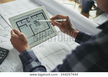 Tablet Computer With Building Plan In Hands Of Architect
