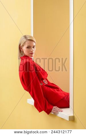 Pensive Fashionable Woman In Red Suit Looking Out Decorative Window