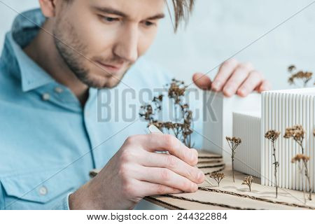 Selective Focus Of Focused Architect Looking At Self Made Building Model In Office