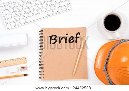 Brief Concept. Top Viwe Of Modern Workplace With Safety Helmet, Office Supplies, A Cup Of Coffee And
