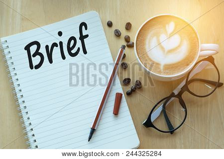 Concept Brief On Notebook With Glasses, Pencil And Coffee Cup On Wooden Table