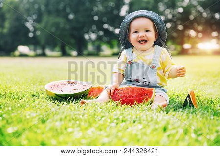 Baby Girl Eating Watermelon On Green Grass In Summertime On Nature