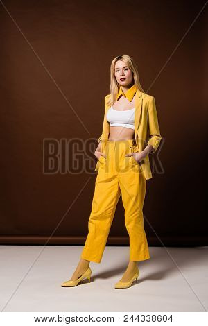 Beautiful Blonde Woman In Stylish Yellow Clothes Standing With Hands In Pockets And Looking At Camer