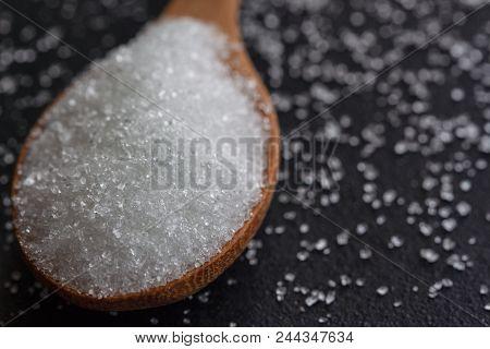 Natural Purified Sugar Or Bleach Sugar On Wood Spoon. White Bleach Sugar On Black Granite Table In C