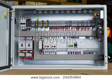 Modern electrical control Cabinet with controller and circuit breakers. Motor protection switches. Contactors with thermal relays. Fuse-operated breakers. Through terminals. Connecting wires. poster