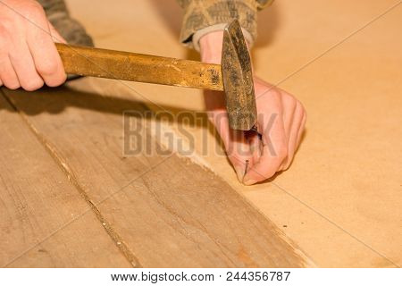 A Man Is Hammering Small Nails. Hammer A Nail Board With A Hammer.