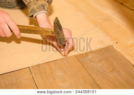 A Man Is Hammering Small Nails.