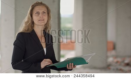 Female Architect Studying Drafts While Visiting Large Construction Site Professional
