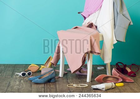 Messy Room With Elegant Fashionable Clothes And Shoes On Chair